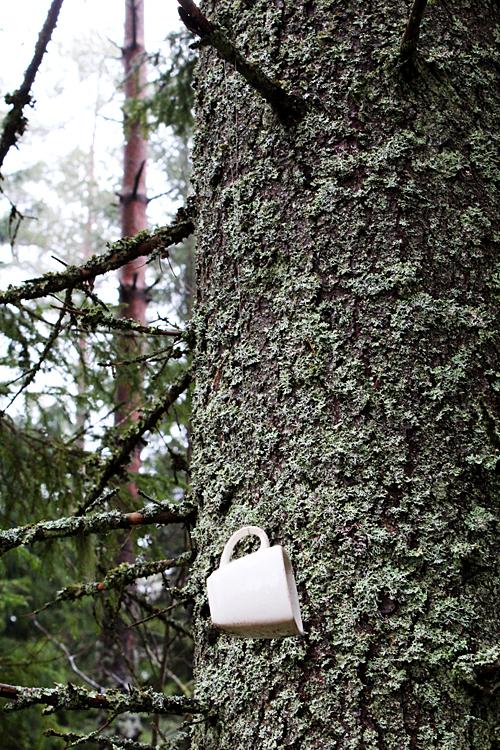 En kaffekopp mitt ute i naturen hängandes på ett snöre